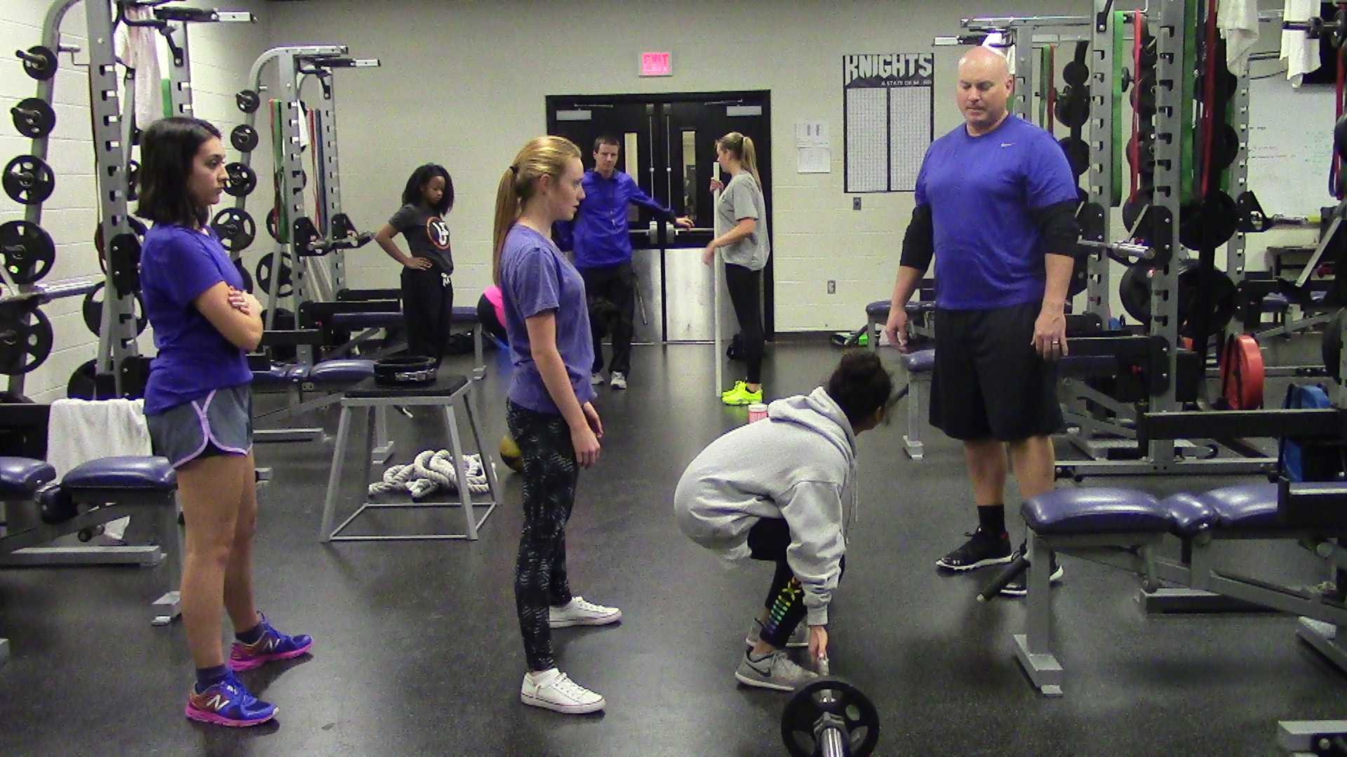 Coach Walker checks if the female powerlifters are using proper lifting techniques. He does this to make sure they'll be ready for any co-ed competitions, meets or even practices.