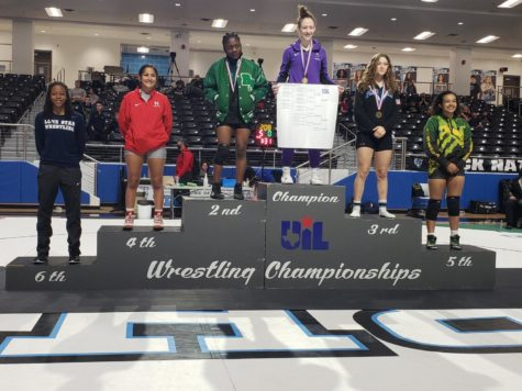 Tabitha Wood stands on top of the podium after finishing first in her weight class at regionals. This win qualified her for the state wrestling meet. (Knight Press/IHS Knight Press Twitter)