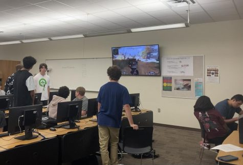 Esports students work on assignments while they participate in a videogame tutorial.